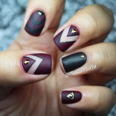 Black and maroon nail art design. The design is tribal inspired with various shapes In alternating colors and topped with gold embellishments for accent.