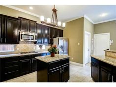 Dark wood cabinetry // Light countertops // Stainless-steel appliances