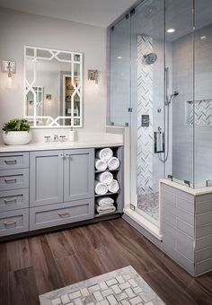 corner bathroom idea with grey cabinets white countertop mirror with white decorative frames medium tone wood floors grey subway tiles shower walls and floors glass panel door