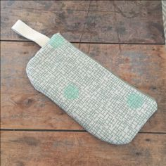 heavy canvas material with graphic sage and mint print: Skinny Laminx Sage nylon zipper woven handle lined with queen anne's lace printed quilting cotton in a pale green Interior pocket Measures 13 inches wide (not including handle), by 6.5 inches tall