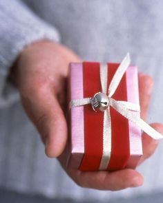 Jingle Bells Wrap...  Re-create the sound of Santa's sleigh with a small bell attached to Christmas parcels. Purchase the bells at crafts stores, and use lengths of thin ribbon or cord to secure to packages. The box shown here is also decorated with a band of velvet ribbon.