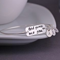 """Each bangle is hand formed from sterling silver wire, then hammered and tumbled for shine and strength. A stainless steel rectangle is engraved with """"God gave me you"""" and measures 1 inch across. Bangl"""