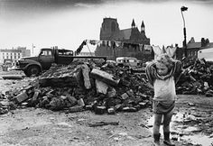 Photograph by Shirley Baker. A young traveller girl stands amid the rubble of a cleared area of dilapidated terraced housing in Manchester. 1968