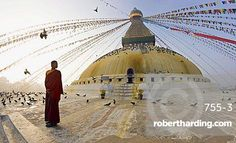 Young Buddhist monk turns to look at the dome of Boudha (Bodhnath) (Boudhanath) Tibetan stupa in Kathmandu, UNESCO World Heritage Site, Nepal, Asia