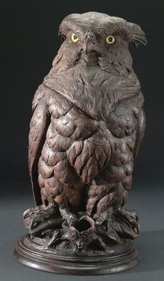 A LARGE AND IMPRESSIVE BLACK FOREST CARVED, FIGURAL WALNUT HUMIDOR OF AN OWL C. 1900. Life sized, carved in full round and set with glass eyes. The head reveals a hollowed chamber, an integral carved match receptacle extends from base. Height 19 inches.