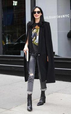 Krysten Ritter wearing a rocker print Def Leppard t-shirt, a black longline cape, dark sunglasses, gray jeans, and black leather mid-calf booties