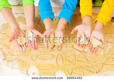 child's hands with dough over the table, top view