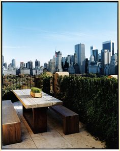 A glamorous cityscape seen from one of the terraces, set with a Balinese teakwood table and benches designed for the apartment by Bonetti Kozerski Studio, NYC.