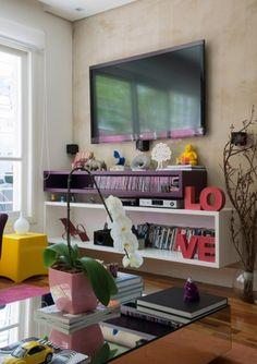A TV está afixada em uma parede de drywall, que esconde os fios dos aparelhos. A parede foi pintada com tinta que imita cimento queimado    Da Revista TPM: http://revistatpm.uol.com.br/revista/128//ana-mouawad-queiroga.html#6