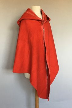 Short cloak, c. 1770. The red broadcloth cut shorter and curved at the back, lengthening at the front, a horizontal join seam the large hood with radiating fan type pleating to the back, inside lined with scarlet sik, similar edging to the hood and front of the cloak.