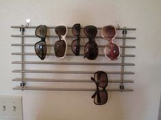 Sunglass display - IKEA Hackers ~ Needed a quick, cheap way to hang your sunglasses?…Ikea hack comes through! 3M Command hooks (no damage to the apt walls) and a little used IKEA LÄMPLIG Trivet (cooling rack) Read more at http://www.ikeahackers.net/2014/07/sunglass-display.html#kWFkTjLTDMr8vDmQ.99
