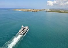 An aerial view of a yard boat ferry crossing the harbor at Naval Station Guantanamo Bay, Cuba.