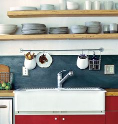 A thin, wall-mounted metal bar above the kitchen sink holds cooking, cleaning, and decorative elements and keeps them off the countertop.