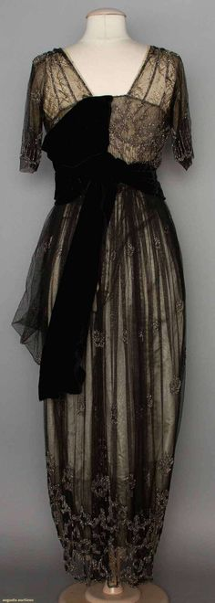 "BEADED EVENING GOWN, 1911-1912 | New York City | 2-piece, black net over cream satin, net trimmed in cut steel beads, petersham labeled ""Dunstan Inc. 24 West 57th St New York"""