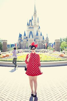 She looks like Minnie Mouse! What a pretty red polka dot dress and mouse ears outfit for a day at Tokyo Disneyland.