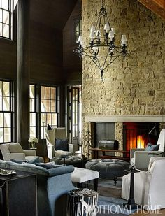 A giant stone wall in this great room is home to a fireplace and an understated mantel. - Traditional Home ® / Photo: Emily Jenkins Followill / Design: Susan Ferrier
