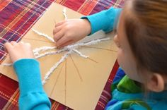 sandpaper snowflakes - yarn and small pom poms naturally cling to sandpaper's gritty surface making for a mess free craft project!