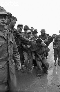 South Vietnam. Hue, 17 Feb 1968. U.S. Marines guarding Viet Cong prisoners captured during battle for Hue. The prisoners are to be kept at a detention area.