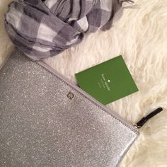 """HP SALEKate spade silver glitter clutch Brand new with tag. Never used. Glittery smooth exterior. Nylon interior printed with """"kate spade."""" Works as a clutch or cosmetic bag. 7.5""""x10.25"""". AND...see that adorable scarf? It's for sale in my closet! If you bundle items in my closet you get a lovely discount  kate spade Bags Clutches & Wristlets"""