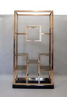 1970s design bookcase in gilt metal with smoke glass shelves, on black laminated base.  Good condition