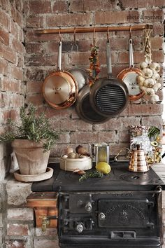 Brick kitchen, iron stove and hanging copper pans