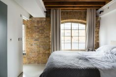 Warehouse conversion in London. All of the finishes of the new walls and joinery are plain and monochromatic, acting as a canvas for the texture of the brick and timber. Sliding pocket doors prevented the need for architraves on the existing brick walls, allowing them to connect spaces through door openings.