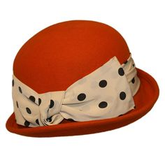 Palarie bowler hat din fetru caramizie Aceasta palarie bowler hat din fetru caramizie este prevazuta cu banda textila lata alba cu buline negre, imbinata intr-o funda supradimensionata. O excelenta alegere pentru o tinuta casual, dar stylish.