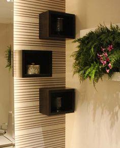 Nichos sobre o papel de parede listrado, parede espelhada e um jardim vertical formam o visual moderno e sofisticado do lavabo projetado pela arquiteta Larissa Baptista Cassani.
