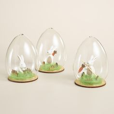 Each in a different pose - digging up, fishing with or hiding a carrot - our charming bunnies are enclosed in egg-shaped glass cloches and accented with real wood details.