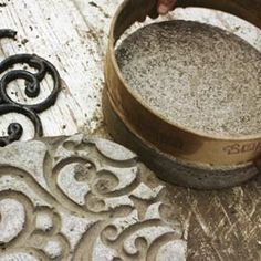 DIY Concrete stepping stones using cut rubber door mats for scrollwork impression.