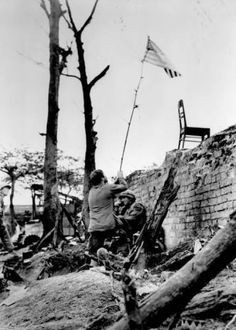 A US Marine waves an American flag tied to a tree branch before securing it on the brick wall of a citadel in Hue, Feb. 1968; The Marines charged the wall while under fire to secure the flag here as fighting continues in the old imperial fortress for the third straight week.