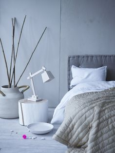 LOVE that headboard - looks like a giant floor pillow. Suppose you could DIY something like that... Also love the big pot with the sticks - something about bare branches that is just beautiful and the detail on the handle there is great.