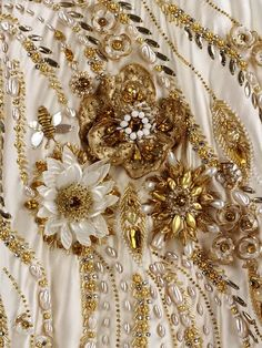 Detail of a gown worn by Queen Elizabeth in Paris, 1957. The dazzling, jewel-like details of the embroidered design include miniature BEES, grasses, wheat and wild flowers.