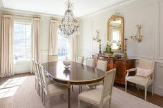 French dining room boasts a crystal chandelier illuminating an oval French dining table with gold trim lined with gray linen French square back dining chairs placed atop a light gray bound sisal rug centered in front of windows dressed in light gray curtains accented with blue trim.