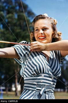 41add6020 Stock Photo - 1940s 1950s SMILING TEEN GIRL ARCHER WEARING BLUE AND WHITE  STRIPED DRESS SHOOTING AIMING BOW AND ARROW