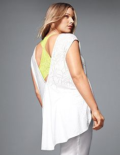 A favorite piece for trendy layered looks, our botanical burnout tee is a unique topper to your favorite tank or cami with its open back design. Solid back inset flows into a high-low hem - just right with leggings! Finished with raw edged trim at V-neck and back and cap sleeves. lanebryant.com