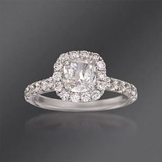 A beautiful Henri Daussi halo-styled 1.52 ct. t.w. diamond engagement ring, which could also be a wedding ring or suitable as a gift for another celebration. It features a central cushion-cut diamond totaling .72 carats, haloed in .80 ct. t.w. of magnificent pave diamond rounds which also sparkle along the band.  14kt white gold ring.