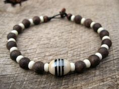 Mens surfer bracelet handmade from bone, glass and wood beads threaded onto strong cord with a toggle and loop clasp. Beaded tribal surfer style