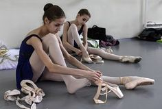Putting on ballet shoes before a classical ballet class
