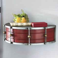 """Do you march to your own beat? Then let your unconventional side take center stage with this unique metal shelf that looks like a snare drum. 153/4""""w x 5""""h x 8""""d. The image shows a silver tone finish. Actually, the shelf has more of a copper/gold tone finish."""