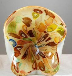 This is a Murano Italian millefiori glass bowl or candy dish done in golds browns and greens. Millefiori refers to the method in which the design is produced whereby mulitple strands of colored glass rods are heated and spun to create the desig...