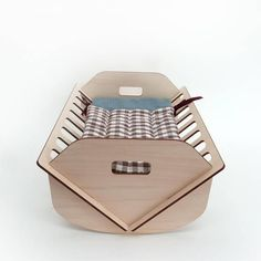 Little wooden crib to rock and sleep the dolls and other soft toys. This crib looks simple and modern and is very smart and useful. A little storage is hidden inside to put the dolls stuff. Flat packed its easy to assemble and carry. The little sleeping bag can be also used to store and