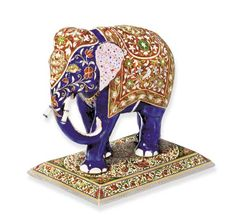 AN INDIAN ENAMEL AND GEM-SET ELEPHANT DESK ORNAMENT The elephant body enamelled in blue with pink spotted ears and trunk, white detail on feet and tusks, ruby eyes, to the ceremonial trappings of multi-coloured enamel set with table-cut diamond floral motifs; on a similar coloured polychrome enamelled rectangular base