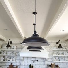 Get up close & personal with a beautiful contrast that pops thanks to this dreamy white kitchen w/ black accents, including Rejuvenation's Baltimore pendants.