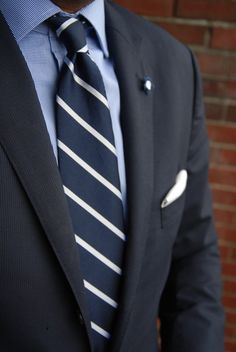 Navy repp striped tie paired with light blue shirt, navy suit, and white pocket square. Communicates strength (really dig that subtle lapel pin).