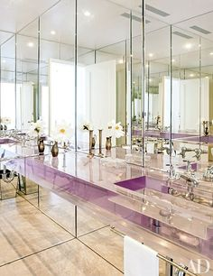 A jewel-like powder room featuring mirrored cabinets and a clear-resin sink and counter | archdigest.com