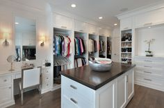 Fabulous walk-in closet features pull up cabinets stacked over double stacked clothes racks across ...