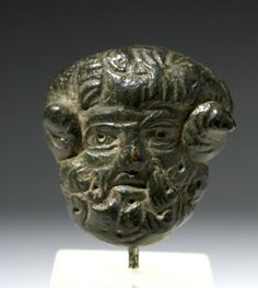 Roman Empire, ca. 1st to 3rd century CE. A miniature bronze cast applique depicting the head of Pan, the beloved half man half goat horned god known for his hunting skills. The details of Pan's expressive visage - those staring eyes, pointed ears, curly coiffure, mustache, and beard - are intricately delineated.