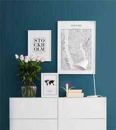 Tavlor ovanför vit byrå i vardagsrummet. Posters i storlekarna 21x30, 30x40 och 50x70cm. Stockholm, New York, Världskarta. Vacker turkos väggfärg.