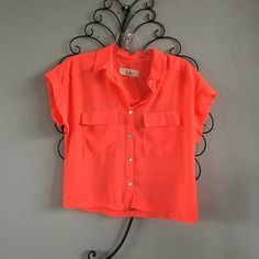 Lola Neon Coral Button-Up Crop Top It is a bright coral color, not orange like the pictures. Lola is BCBG's inexpensive line. Worn once. Never worn, just tried on. Perfect condition, no flaws. Let me know if you have any questions!! Make me an offer!! BCBGeneration Tops Crop Tops